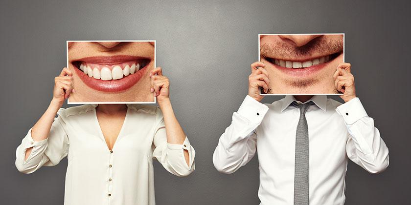 Kvinna och man som håller upp skyltar med leenden framför ansiktet